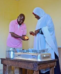 Hillary Njau demonstrates the CLEANCOOK stove in the Zanzibar Pilot Study.